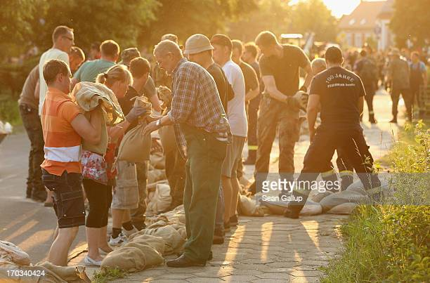 Hundreds of firemen, Bundeswehr soldiers and local volunteers scramble to protect homes with sandbags from the rising floodwaters of the Elbe river...