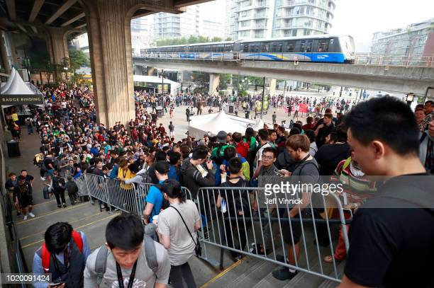 Hundreds of gaming fans stand in line outside Rogers Arena as they wait to enter on the first day of The International 2018 DOTA 2 Championships on...