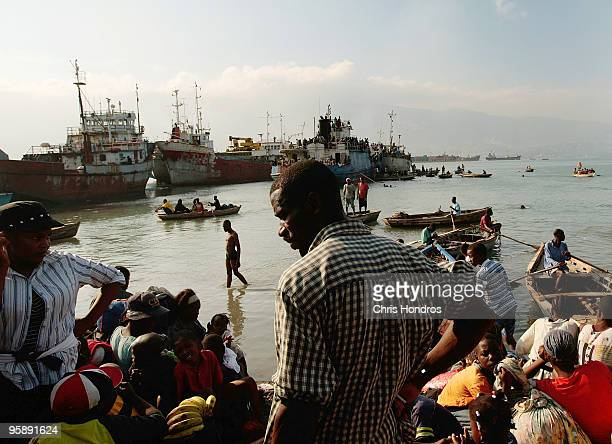 Hundreds of Haitians stand on the shore and on a crowded ship docked off the coast January 20 2010 in PortauPrince Haiti Thousands of...