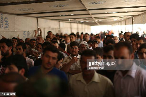 Hundreds of Iraqi's wait to register at a temporary displacement camp for Iraqis caughtup in the fighting in and around the city of Mosul on June 26...