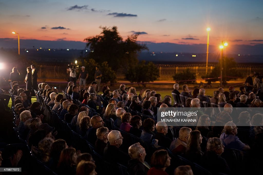 Hundreds of Israelis attend a 'cross border peace concert' in the Kibbutz Kfar Aza near the Israel-Gaza Strip border (seen at the back) on June 4, 2015 one year after the lastest war between Israel and Palestinian militans. The two-part concert, participated by hundreds of Israelis and three Gazans, was an attempt to echo the struggle of southern Israeli residents, and 'bring an end to the bloody conflict between Israel and Gaza and to set out on the path of a political solution,' according to organisers.