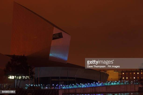 Hundreds of joggers wearing special suits with led lights attached arrive outside the Lowry Theatre in Salford Quays Greater Manchester