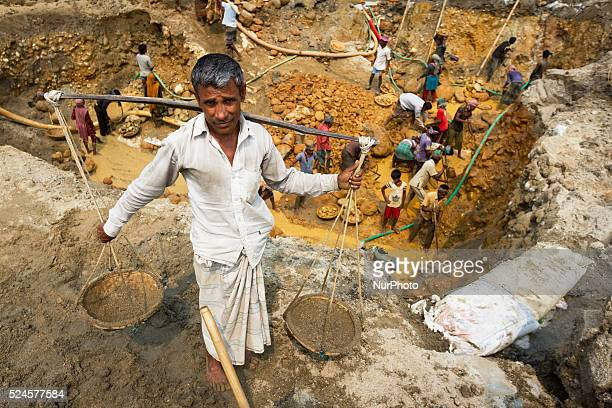 Hundreds of labors are working to extract stone from the reservoir in Sylhet Bangladesh while another old man is collecting sand on February 28 2015...