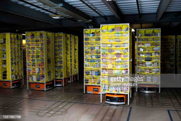 Hundreds of lawnmowersized robots that move around shelving units in a closed field are seen during a tour of Amazon's Fulfillment Center September...