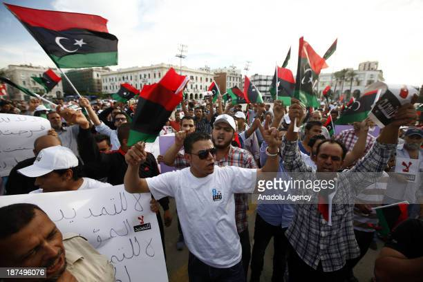 Hundreds of Libyans gathered in Martyrs Square shout slogans and wave national flags during a protest against an extended mandate of the General...