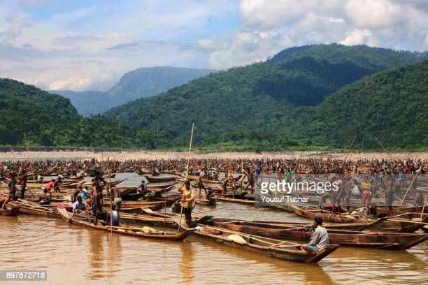 Hundreds of little black and grey boats collecting stones at Jaflong Stone Quarry field The crystal clear water of the Piyain River which flows from...