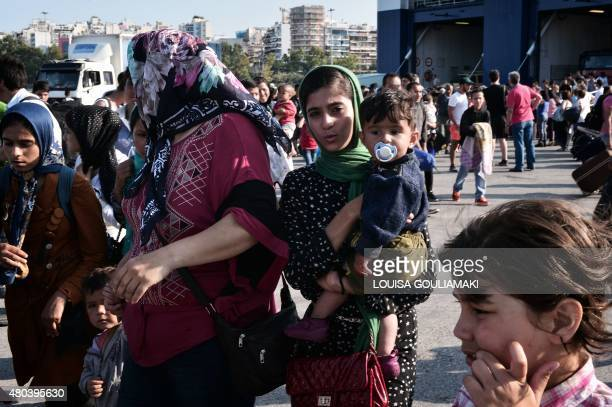 FROISSART*** Hundreds of migrants disembark from a ferry originating from the island on Lesbos at the port of Piraeus near Athens on July 11 2015...