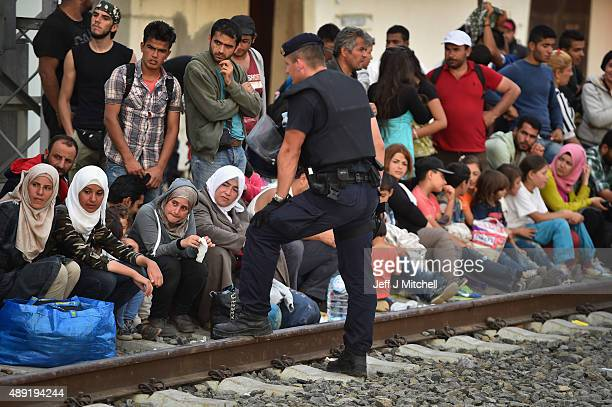 Hundreds of migrants wait for a train to Zagreb from Tovarnik station on their journey north despite moves by Slovenia and Hungary to hold them back...