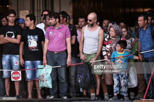 FROISSART*** Hundreds of migrants wait to disembark from a ferry originating from the island on Lesbos at the port of Piraeus near Athens on July 11...