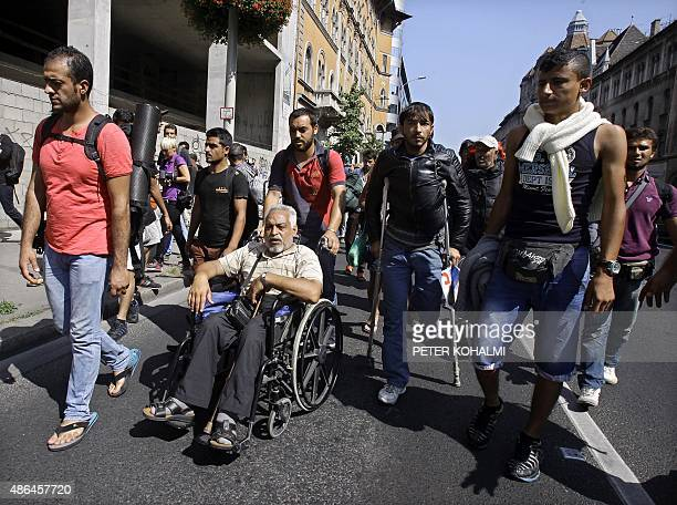 Hundreds of migrants walk across Budapest after leaving the transit zone of the Budapest main train station on September 4 2015 intenting on walking...