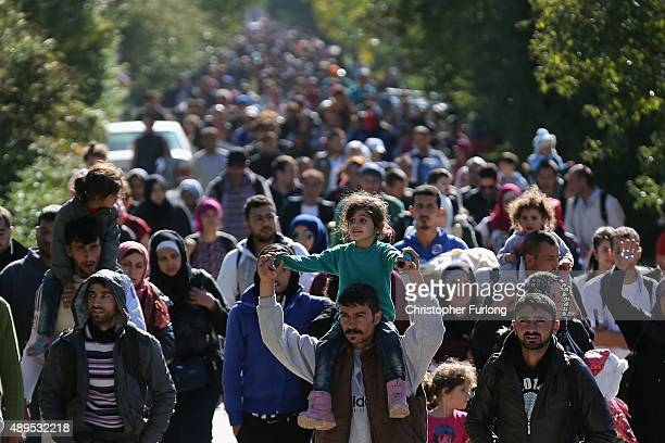 Hundreds of migrants who arrived by train at Hegyeshalom on the Hungarian and Austrian border walk the four kilometres into Austria on September 22...