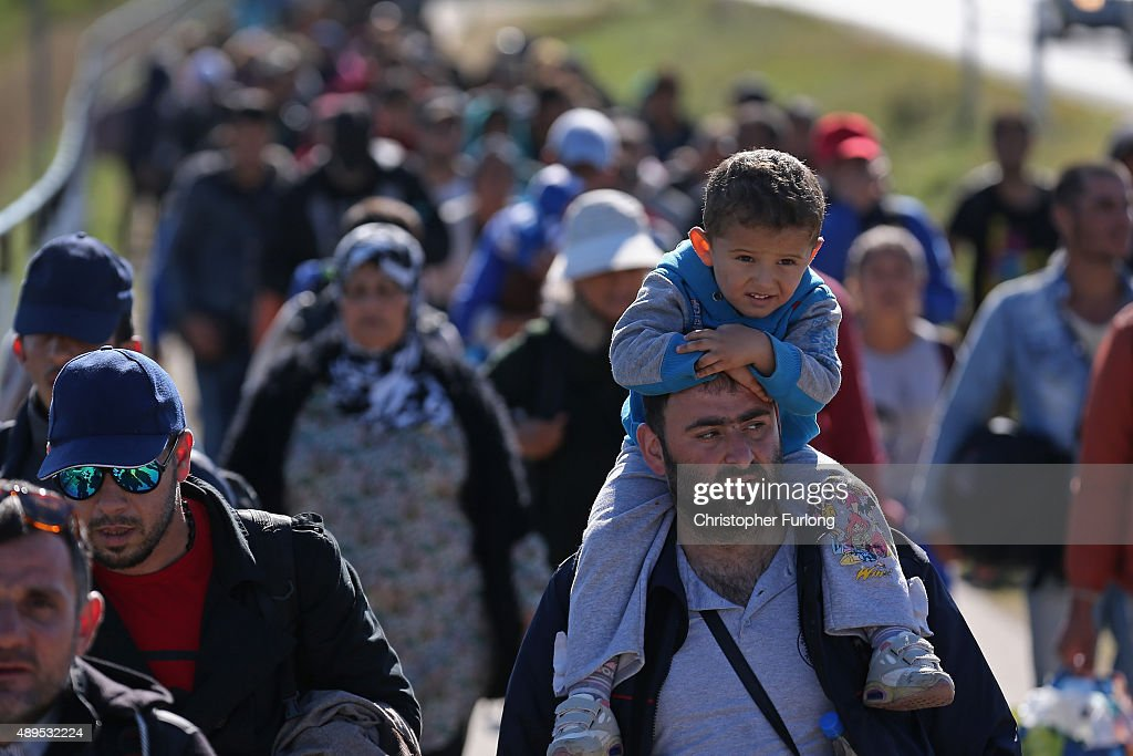 Hundreds of migrants who arrived by train at Hegyeshalom on the Hungarian and Austrian border walk the four kilometres into Austria on September 22, 2015 in Hegyeshalom, Hungary. Thousands of migrants have arrived in Austria over the weekend with more en-route from Hungary, Croatia and Slovenia. Politicians across the European Union are holding meetings on the refugee crisis with EU leaders attending an extraordinary summit on Wednesday to try and solve the crisis and the dispute of how to relocate 120,000 migrants aross EU states.