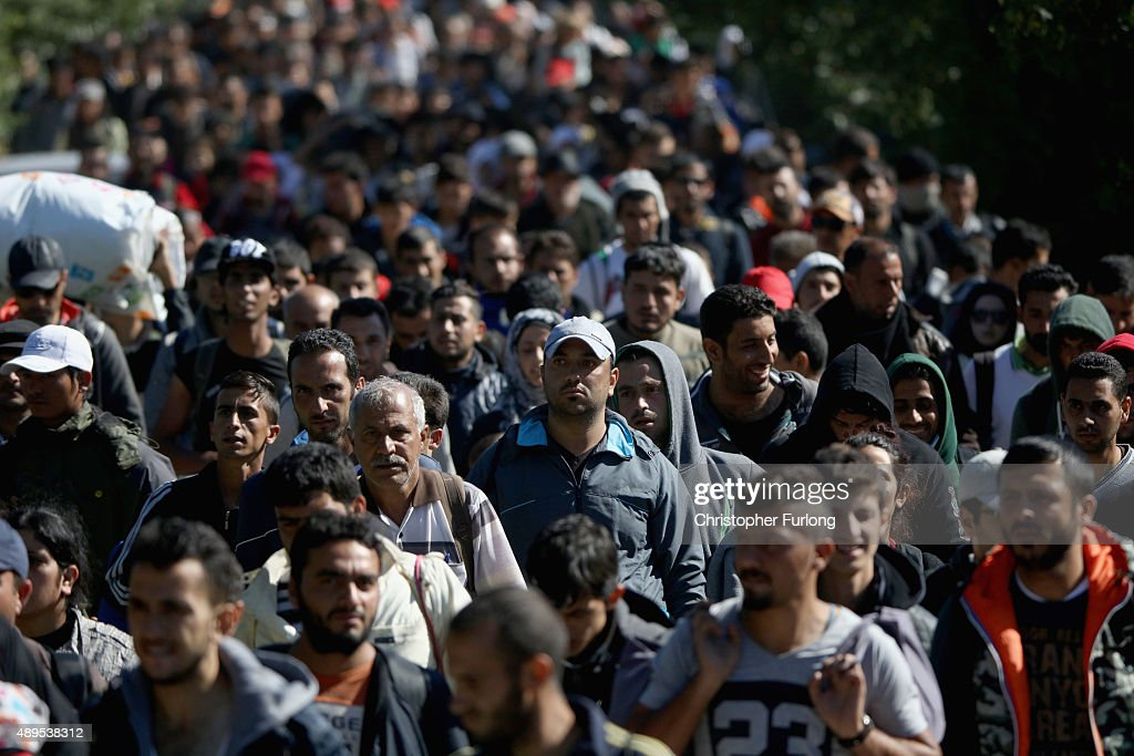 Hundreds of migrants who arrived on the second train today at Hegyeshalom on the Hungarian and Austrian border, walk the four kilometres into Austria on September 22, 2015 in Hegyeshalom, Hungary. Thousands of migrants have arrived in Austria over the weekend with more en-route from Hungary, Croatia and Slovenia. Politicians across the European Union are holding meetings on the refugee crisis with EU leaders attending an extraordinary summit on September 23 to try and solve the crisis and the dispute of how to relocate 120,000 migrants across EU states.