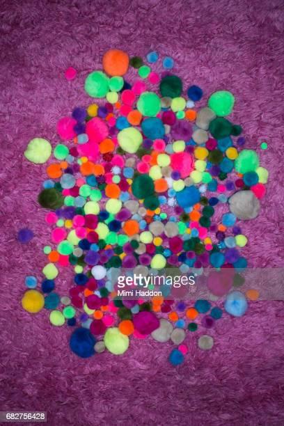 Hundreds of Multi colored Pom-poms on Pink Rug