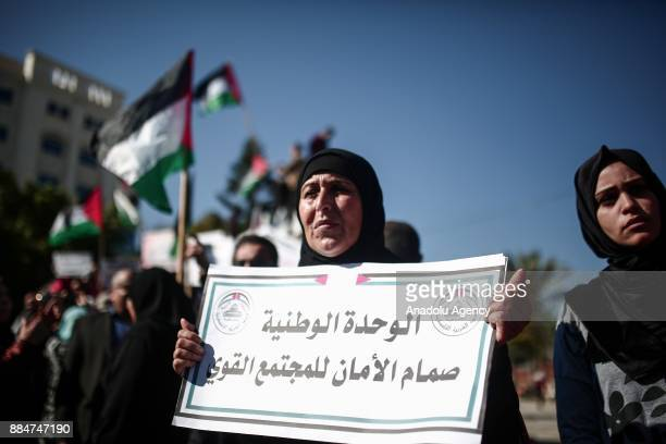 Hundreds of Palestinians hold placards and shout slogans as they gather at alSaraya Square during a march through the Unknown Soldier's monument to...