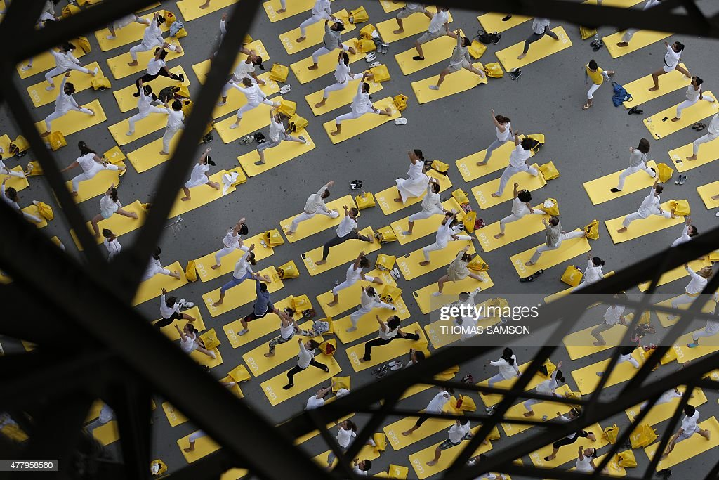 Hundreds of people attend a yoga session under the Eiffel Tower in Paris, on June 21, 2015, in a mass yoga session to mark the first International Yoga Day. 192 countries join the event.