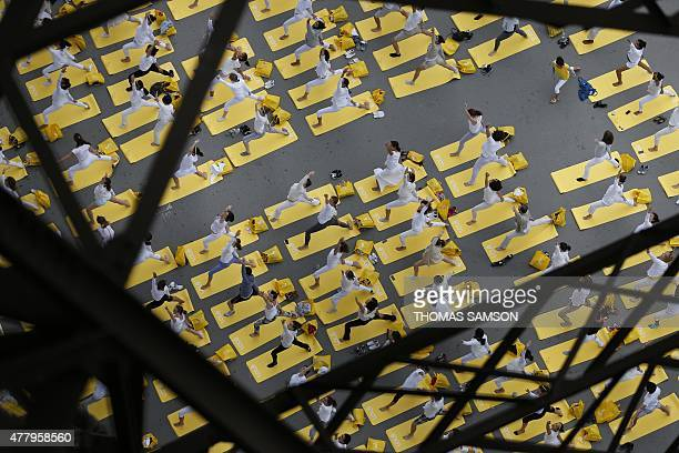 Hundreds of people attend a yoga session under the Eiffel Tower in Paris on June 21 in a mass yoga session to mark the first International Yoga Day...