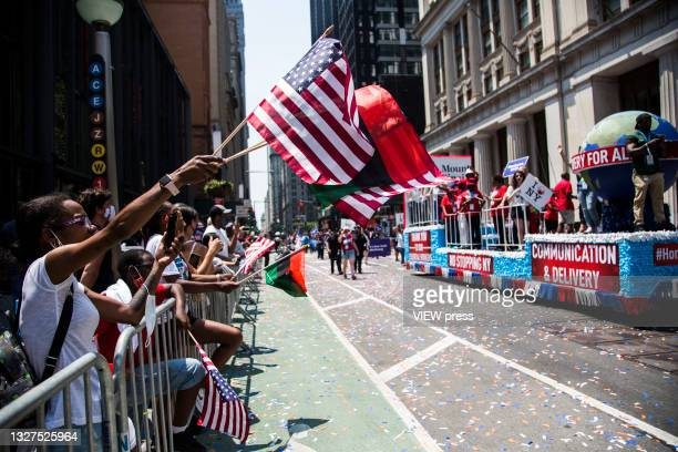 Hundreds of people cheer as police, firefighters, hospitals and other first responders participate in a ticker tape parade to honor workers who...