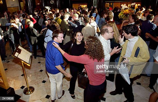 Hundreds of people each pretend to greet a long lost friend as they participate in a flash mob in the lobby of the Westin St Francis Hotel August 20...