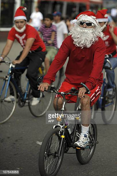 Hundreds of people fancydressed as Santa Claus march with their bicycles along the streets of Cali deparment of Valle del Cauca Colombia on December...
