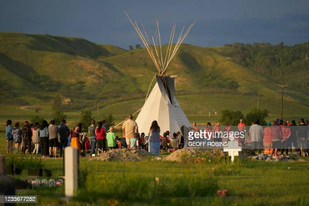 Hundreds of people gather for a vigil in a field where human remains were discovered in unmarked graves at the site of the former Marieval Indian...