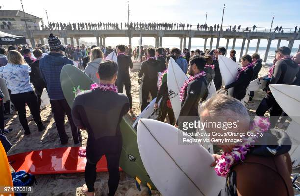 Hundreds of people gather on the sand and on the Huntington Beach Pier during the start of a paddle out to honor Pierre Agnes CEO of Quiksilver in...