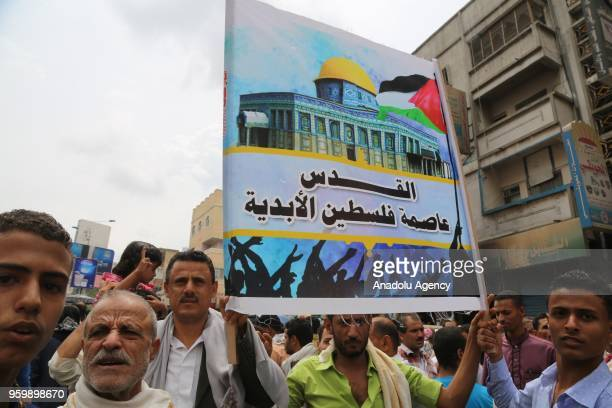 Hundreds of people hold banners and shout slogans as they stage a demonstration to protest against United States' decision to relocate the U.S....