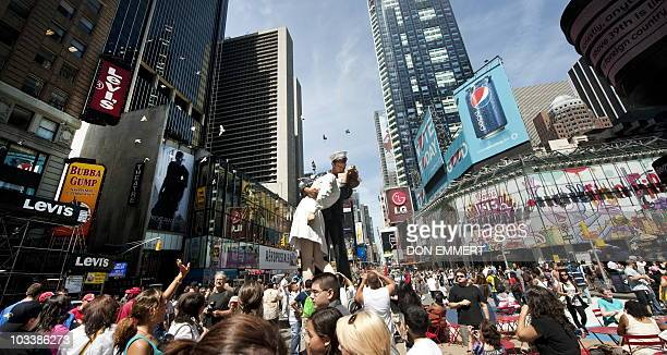 Hundreds of people in Times Square view the a sculpture at the site of the historic LIFE Magazine cover photograph, of an unidentified sailor kissing...