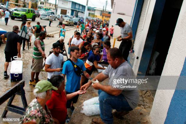 Hundreds of people line up to buy ice at a local plant in the aftermath of Hurricane Maria in Arecibo Puerto Rico September 30 2017 US military and...