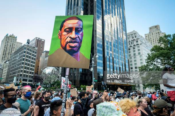 Hundreds of people pack into Columbus Circle to hear speeches against police violence while one of them holds a painted portrait of George Floyd in...