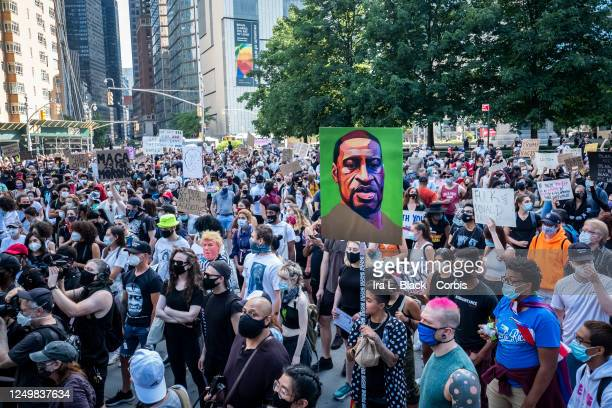 Hundreds of people pack into Columbus Circle to hear speeches of protest against police violence with one protester holding a painted portrait of...