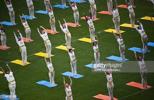 Hundreds of people perform yogic exercises during the World Culture Festival at Berlin's Olympiastadion July 2 2011 Thousands of people showed up for...
