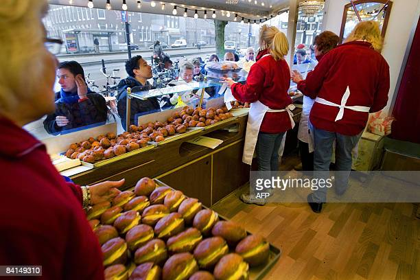 Hundreds of people queue up at the booth of Richard Visser in Rotterdam on December 31 2008 to buy their 'oliebollen' the Dutch traditional fried...