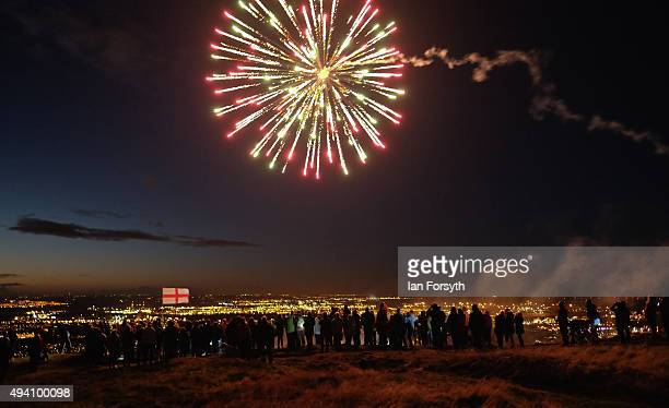Hundreds of people stand looking out over Teesside as a firework is launched into the sky during a torchlit procession on the top of the Eston Hills...