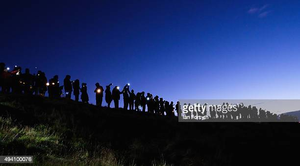 Hundreds of people stand looking out over Teesside during a torchlit procession on the top of the Eston Hills on October 24 2015 in Eston Cleveland...