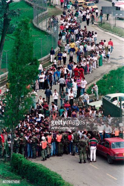 Hundreds of people wait 03 December 1993 outside the cemetery where the body of Pablo Escobar is being viewed Police estimated that some 20000 people...