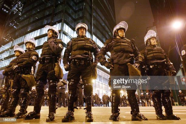 Hundreds of police officers in full riot gear stand watch over anti-war protestors in Chicago's Federal Building plaza following a march through the...