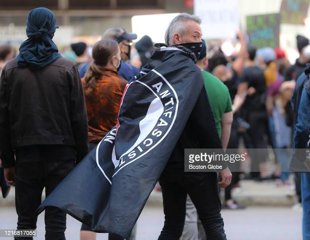 Hundreds of protesters gather at Government Center including a protester with an ANTIFA flag draped over his shoulders during a rally sponsored by...