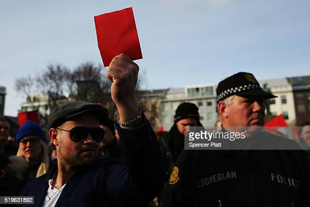 Hundreds of protesters gather in front of the Parliament building holding red cards for a fourth day on April 7 2016 in Reykjavik Iceland Icelandic...