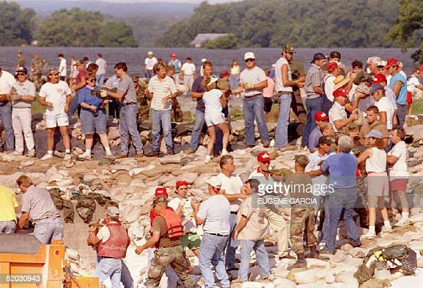 Hundreds of residents form a line as they pass sandbags along a floodthreatened levee 04 August 1993 in a lastditch attempt to save this historic...