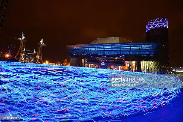 Hundreds of runners in specially commissioned and individually controlled LED light suits create patterns of light outside the Lowry theatre in...