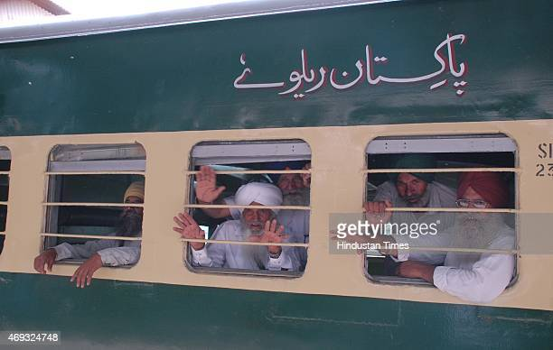 Hundreds of Sikh pilgrims wave from the special Pakistani train as they depart for Lahore to celebrate Baisakhi festival in Pakistan from Amritsar...