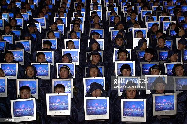 Hundreds of South Korean army soldiers hold flat computer screens to show new technology for the new 2000 year on the main street in Seoul 01 January...