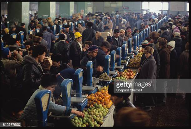 Hundreds of Soviet shoppers pack into the Free Market where produce is plentiful but despite the name the food costs three times as much as state...