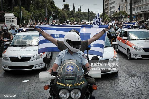 Hundreds of striking municipal police officers drive their motorbikes as a protester holds a Greek national flag during a protest in front of the...