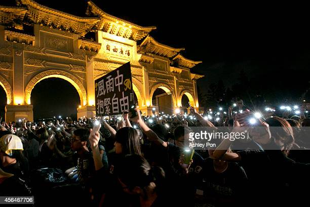 Hundreds of students raise their cell phone with one sign reading hold on to freedom in the rain in front of Liberty Square to show support for Hong...