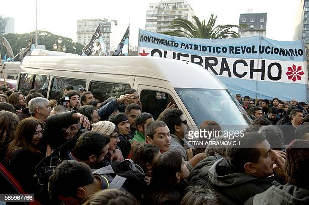 Hundreds of supporters follow a van carrying Hebe de Bonafini leader of the Mothers of Plaza de Mayo human rights organization as she arrives at the...