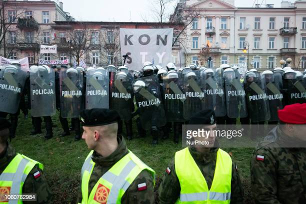 Hundreds of thousands march to celebrate Polish independence in Warsaw . Police and military try to separate protesters with constituion baner from...