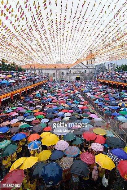 hundreds of umbrellas during a rainy mass at basilica del santo nino - parade stock pictures, royalty-free photos & images