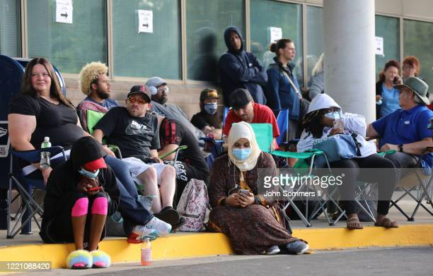 Hundreds of unemployed Kentucky residents wait in long lines outside the Kentucky Career Center for help with their unemployment claims on June 19,...